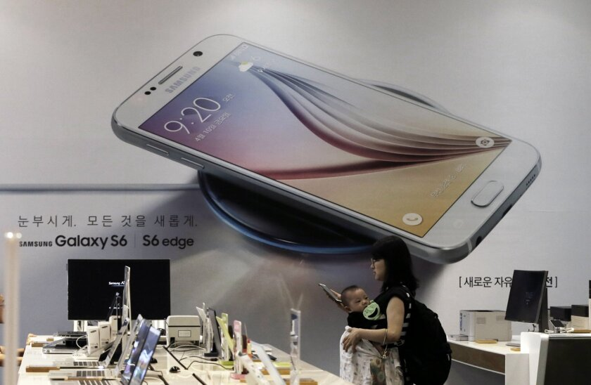 A woman passes by an advertisement of Samsung Electronics' Galaxy S6 smartphone at a Samsung Electronics shop in Seoul, South Korea, Thursday, July 30, 2015. Samsung Electronics reported Thursday a fifth straight drop in quarterly earnings as the Galaxy S6 failed to reverse its declining fortunes in the smartphone industry. (AP Photo/Ahn Young-joon)