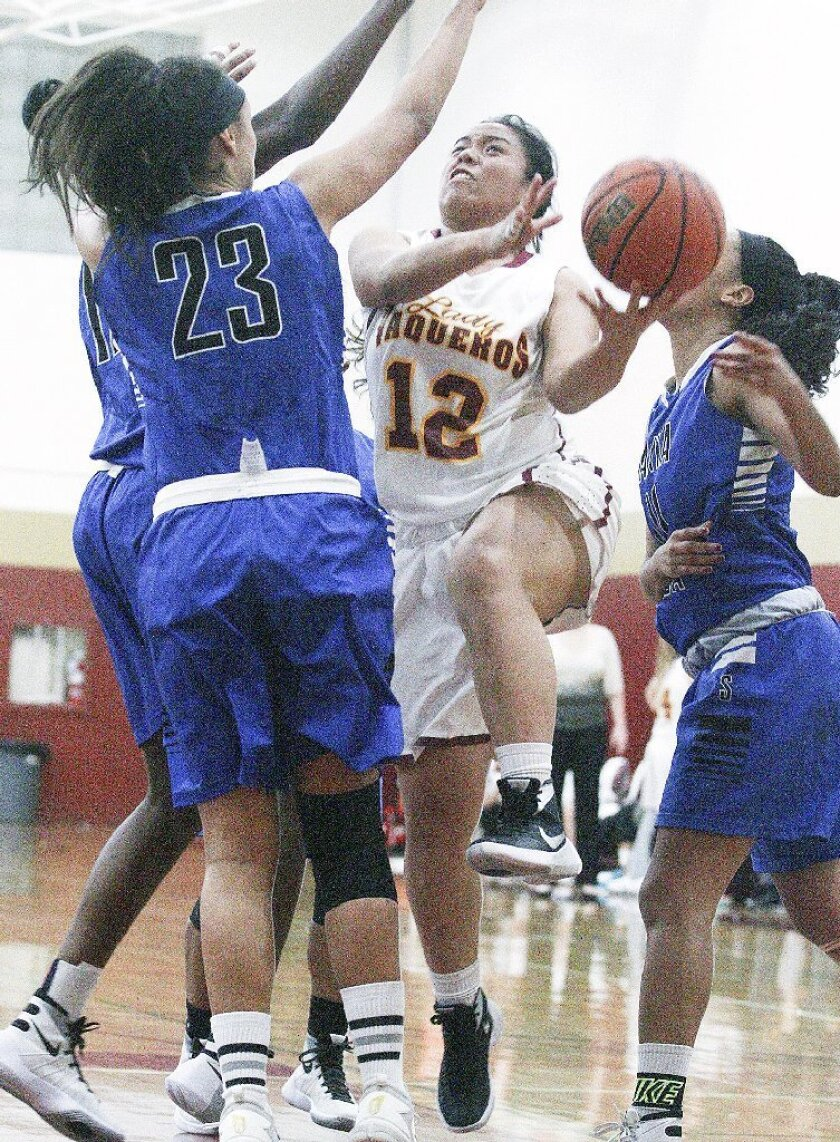 Glendale Community College's Janel Andraneda drives to the basket to shoot against Santa Monica City College's Mammusu Secka and Roberta Hays in a women's basketball game at GCC on Wednesday. (Tim Berger/Staff Photographer)