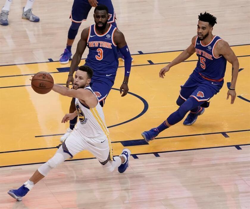 Los jugadores de los Knicks Tim Hardaway Jr. (c) y Courtney Lee (d) luchan por el balón con Stephen Curry (i) de los Warriors durante el partido de la NBA entre los Knicks de Nueva York y los Golde State Warriors celebrado en el Oracle Arena en Oakland, California. EFE