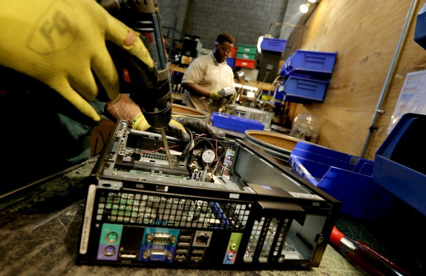 Workers dismantle old electronic equipment at Isidore Electronics Recycling, which Homeboy Industries has acquired and will rename Homeboy Recycling.