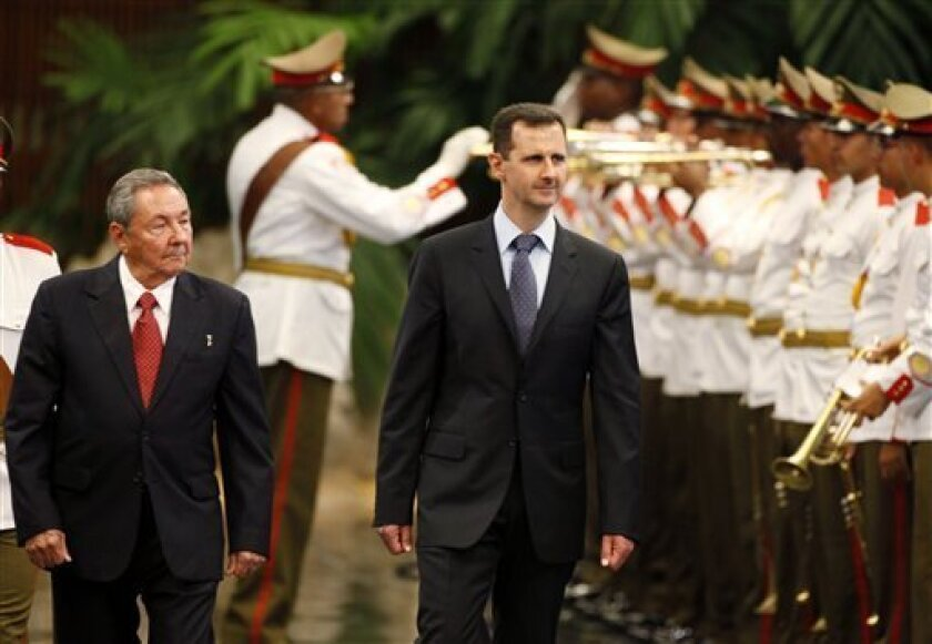 Cuba's President Raul Castro, left, and Syria's President Bashar al-Assad review the honor guard at Revolution palace in Havana, Monday June 28, 2010.  Al-Assad is in Cuba for an official visit. (AP Photo/Javier Galeano)