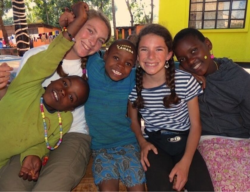 Alex and Lanie Weingarten of Carlsbad, ages 14 and 11, with children at an orphanage in Tanzania in July 2013. CREDIT: Tracey Weingarten