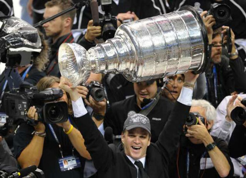 Luc Robitaille hoists the Stanley Cup after the Kings' Game 6 victory Monday.