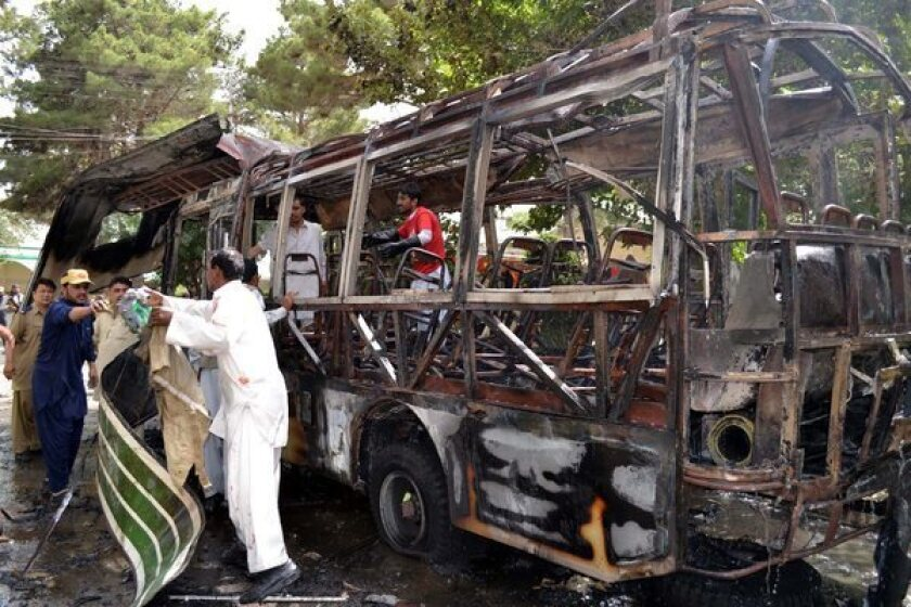Pakistani security officials inspect a university bus after a bomb explosion in Quetta, Pakistan.