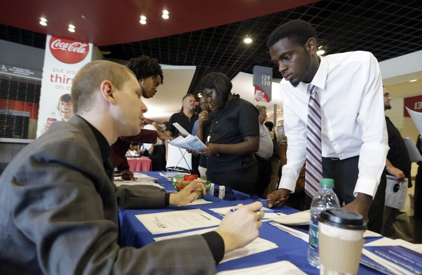 """A job seeker attending a career fair in Sunrise, Fla., in June listens to a representative from Teleperformance, an organization that identifies itself on its corporate website as """"the global leader in outsourced multichannel customer experience management."""""""