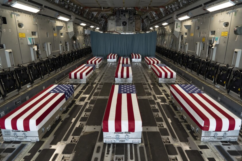 Flag-draped transfer cases carrying the remains of troops killed in Afghanistan line the inside of a transport plane