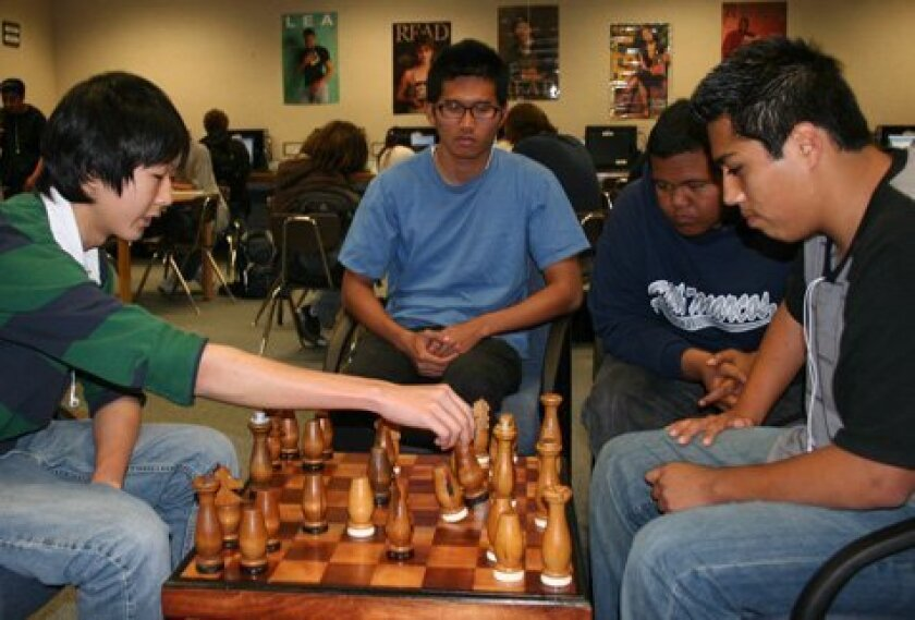 Sowoong Park (left) and Francisco Sotelo play chess while Daryl Agustin and Pierson Cepeda watch. (Pat Sherman)