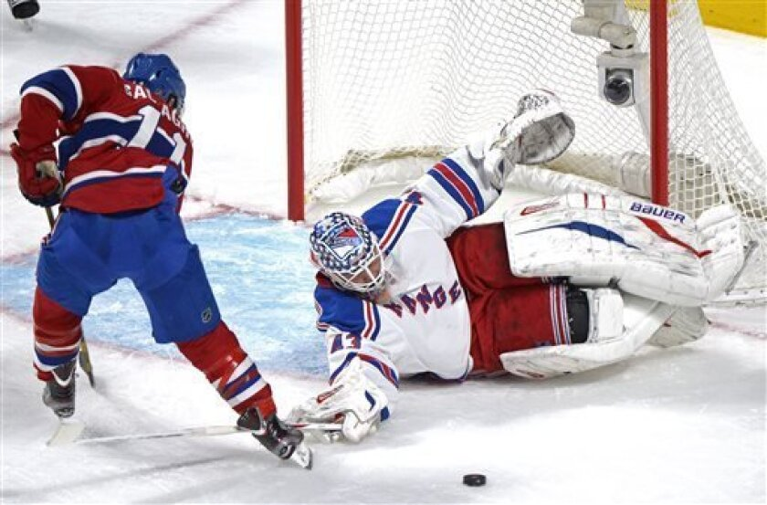 New York Rangers goaltender Martin Biron, right, makes a save against Montreal Canadiens' Brendan Gallagher during second-period NHL hockey game action in Montreal, Saturday, March 30, 2013. (AP Photo/The Canadian Press, Graham Hughes)