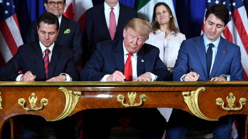 Former Mexican President Enrique Pena Nieto, President Trump and Canadian Prime Minister Justin Trudeau sign a trade agreement in 2018.