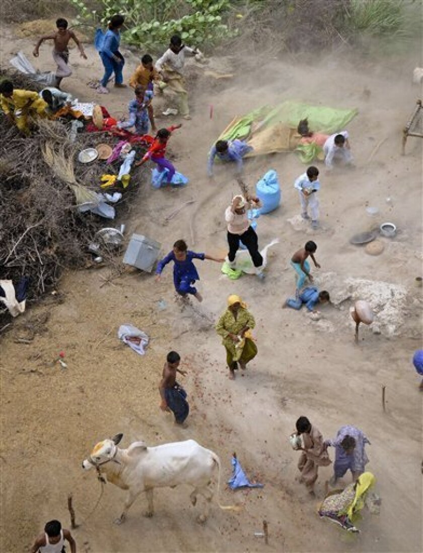 Pakistani villagers rush to collect relief supplies dropped from an army helicopter in a heavy flood-hit area of Mithan Kot, in central Pakistan, Monday, Aug. 9, 2010. The government has struggled to cope with the scale of the disaster, which has killed at least 1,500 people, prompting the internat