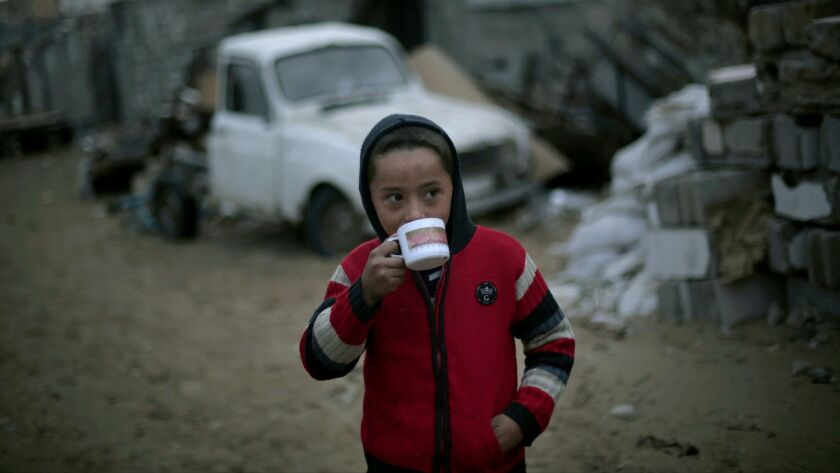 A Palestinian boy drinks hot tea outside his family's house during rainy, cold weather in a slum on