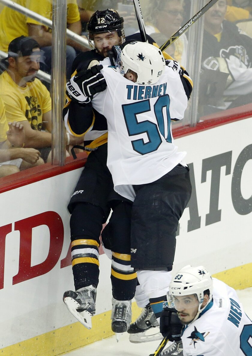 San Jose Sharks' Chris Tierney (50) checks Pittsburgh Penguins' Ben Lovejoy (12) into the boards during the first period in Game 2 of the NHL hockey Stanley Cup Finals on Wednesday, June 1, 2016, in Pittsburgh. (AP Photo/Gene J. Puskar)