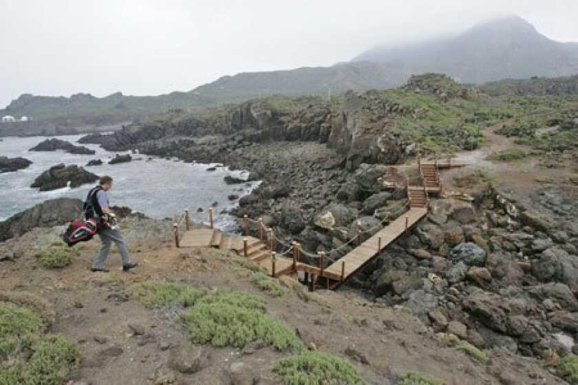 Punta Brava sales representative Ryan Osterdorf walked off a small island that will be the tee box for the 17th hole. (John Gibbins / Union-Tribune)