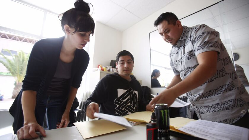 Immigration attorney Nicole Elizabeth Ramos, with assistants Jorge Hernandez and Rigo Martinez, finish up paperwork for asylum seekers about to ask for protection at the U.S.-Mexico border. Ramos has been vocal about reporting cases of asylum seekers allegedly being turned away.