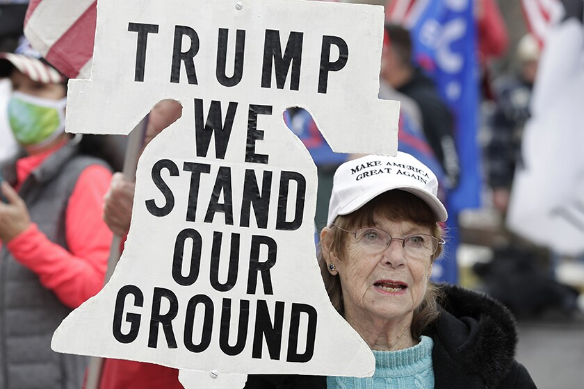"A Trump supporter attends a rally with a bell-shaped sign saying, ""Trump we stand our ground."""