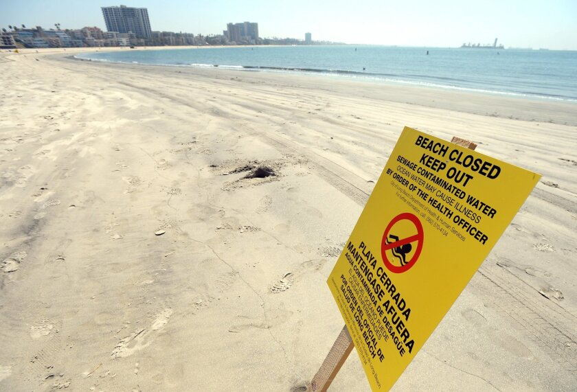 A sign is posted at Alamitos Beach warning of the dangers of sewage contaminated water Tuesday, July 19, 2016, in Long Beach, Calif. Beaches in Long Beach have been shut down after a sewage spill that began near downtown Los Angeles the day before, flowed down the LA River to the ocean. Long Beach