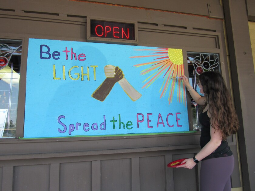 Painter Samantha Razoky works on a mural at the La Mesa Springs Shopping Center.