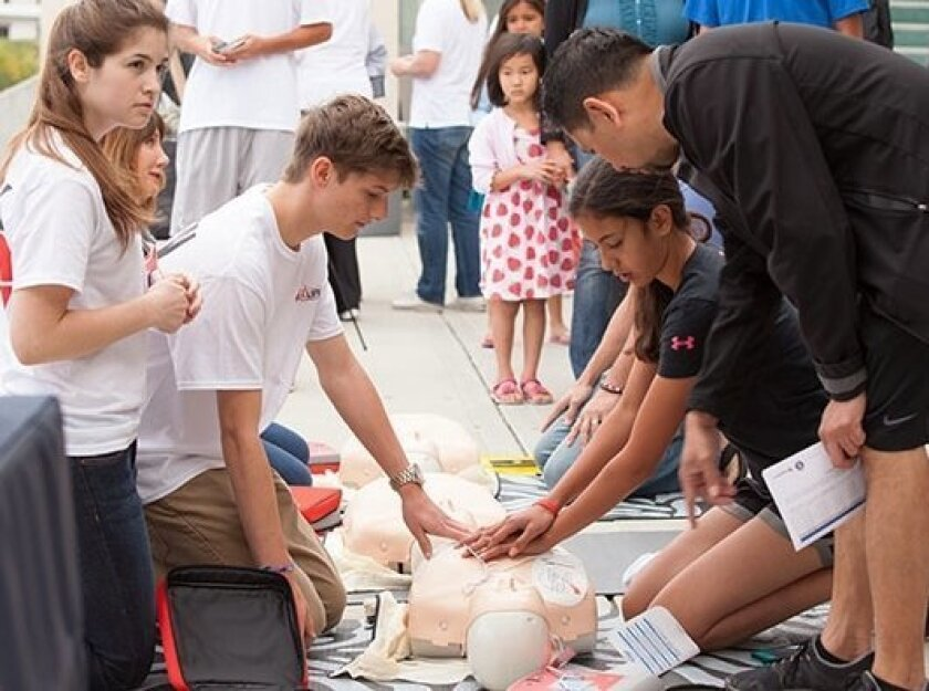 A heart defect screening saved the life of student Devin Lawson, in white T-shirt leaning over CPR dummy. He gives back by teaching CPR at free teen heart screening sessions like this one.