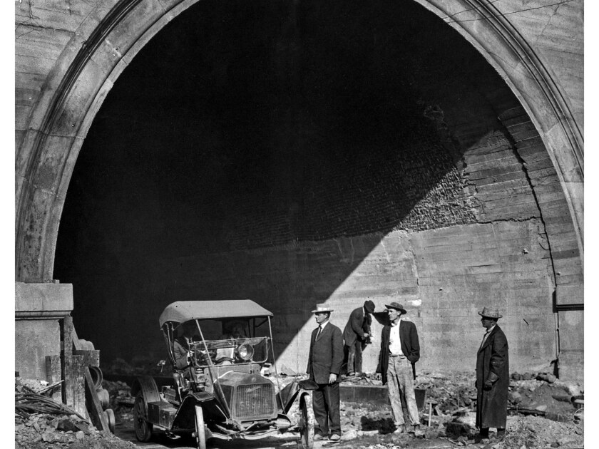 March 22, 1913: Contractors H.A. Wattson and C.A. Spcer drive automobile out of the Hill street tunnel a few minutes after a steam shovel had removed the last foot of dirt.