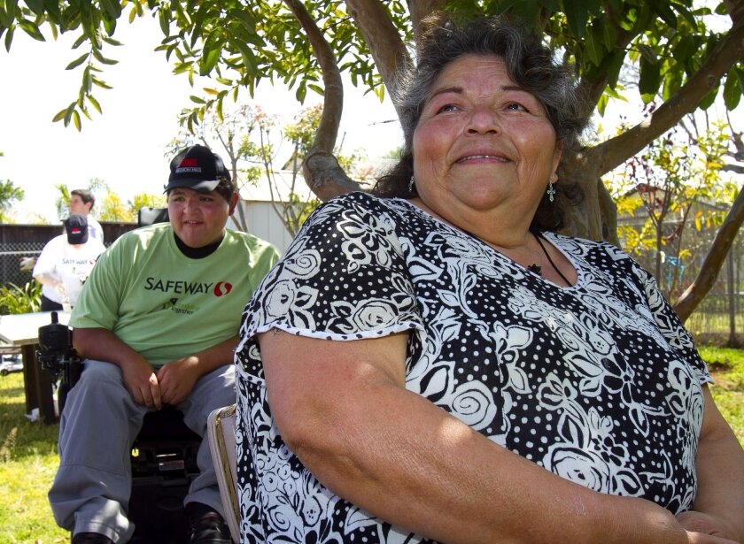 Esperanza Velazco and her son, Willie, watch as volunteers renovate her home in National City. Willie has muscular dystrophy and was having trouble living in his own home. Vons employees, along with Easter Seals and Rebuilding Together San Diego volunteers helped raise $25,000 to perform the renovations, including an accessible shower and a wheelchair ramp.