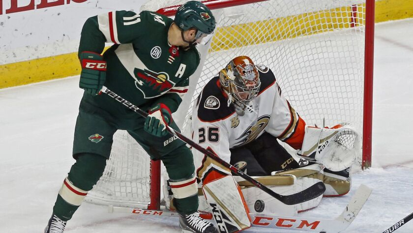 Ducks goalie John Gibson, right, stops a scoring attempt by Minnesota Wild's Zach Parise in the first period.