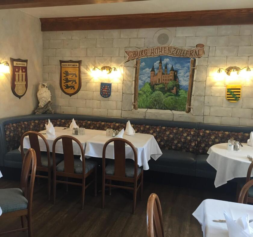 The interior decor at Kaiserhof Restaurant features German/Bavarian family images of the Old World.
