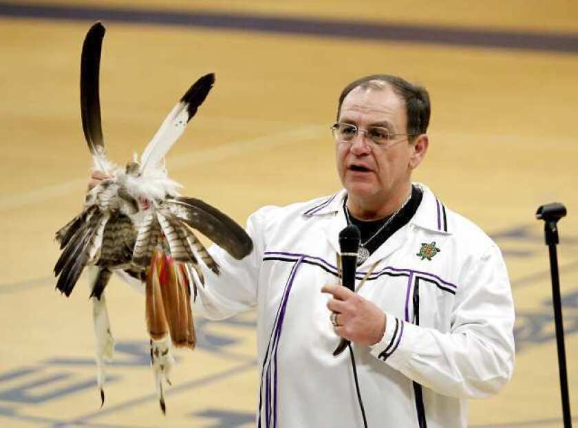 Brian Patterson, a Native American, shows his headdress from the Bear Clan as he speaks to the Newport Harbor High lacrosse players and their families Monday.