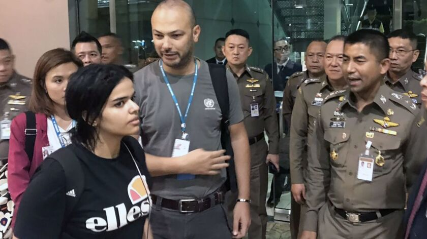 Saudi national Rahaf Mohammed Alqunun, 18, left, with Thai immigration chief Surachate Hakparn, right, at the Suvarnabhumi International Airport on the outskirts of Bangkok on Jan. 7, 2019.