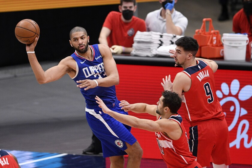 Clippers forward Nicolas Batum makes a pass as he's pressured by Washington's Deni Avdija and Raul Neto.