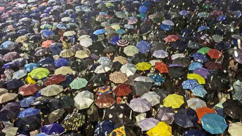 Pro-democracy protestors use umbrellas to shield themselves from heavy rain in Hong Kong on Sept. 30.