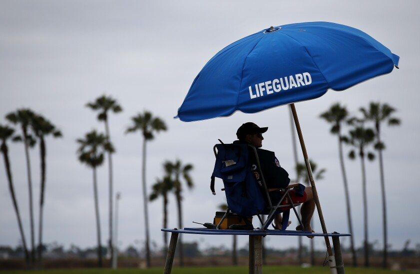 San Diego Lifeguard Tyler Holt looks over Leisure Lagoon in Mission Bay on June 20, 2019. Overcast skies and mild temperatures were in store for much of San Diego for the first day of summer.
