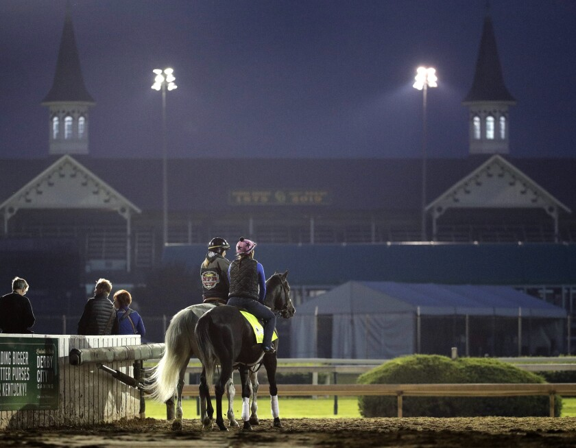 Kentucky Derby hopeful Gray Magician, right, is led onto the track for a workout at Churchill Downs on Tuesday.