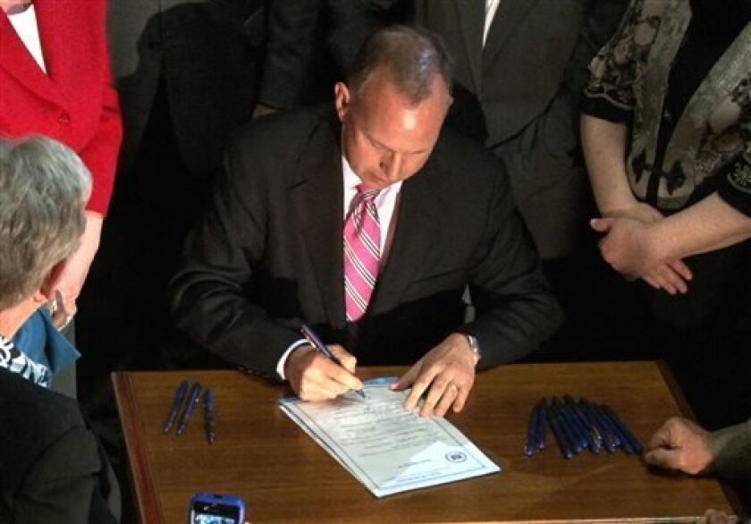 Delaware Gov. Jack Markell signs the marriage equality bill on the steps of Legislative Hall in Dover, Del. on Tuesday, May 7, 2013, after it was approved by the Delaware Senate earlier that afternoon. (AP Photo/The Wilmington News-Journal, Daniel Sato) NO SALES