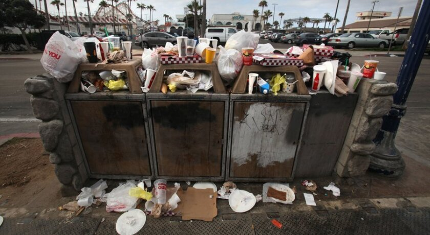 Trash, including plenty of plastic bags, overflows from bins at Belmont Park in Mission Beach.