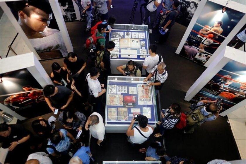 Filipino fans view memorabila during a tribute for the late Muhammad Ali at a shopping mall in Quezon city, east of Manila, Philippines, 10 June 2016. Born Cassius Clay, boxing legend Muhammad Ali, dubbed as 'The Greatest,' died on 03 June 2016 in Phoenix, Arizona, USA, at the age of 74. A public funeral procession and memorial service will be conducted 10 June 2016 in Louisville. EPA/FRANCIS R. MALASIG