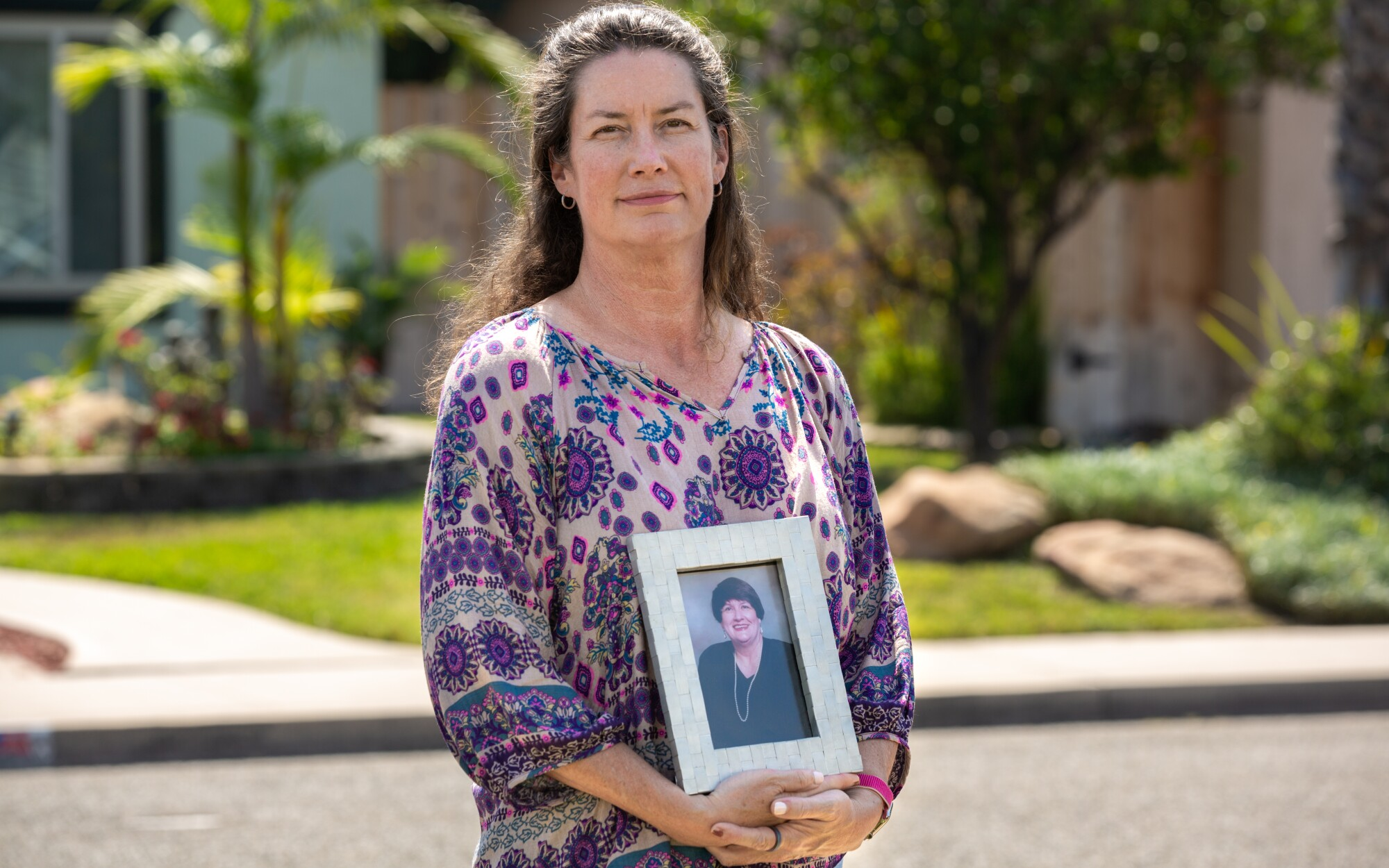 Shannon Svensen holds a photograph of her mother, Modena Svensen in front of their home in Chula Vista.