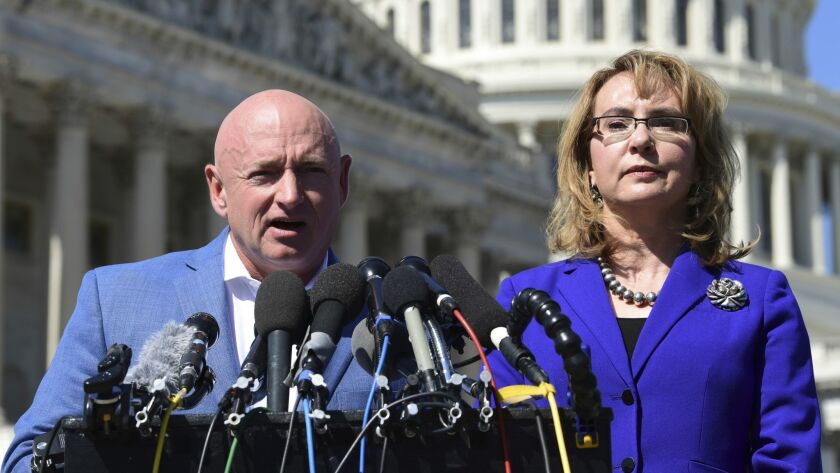 Former Rep. Gabrielle Giffords listens as her husband, Mark Kelly, speaks on Capitol Hill on Oct. 2, 2017.