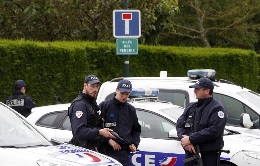 Agentes de policía bloquean el acceso a la calle que lleva al lugar donde un atacante, armado con un cuchillo, apuñaló a un comandante del cuerpo en el exterior de su casa en Magnanville, al oeste de París, el 14 de junio de 2016. (AP Foto/Thibault Camus)
