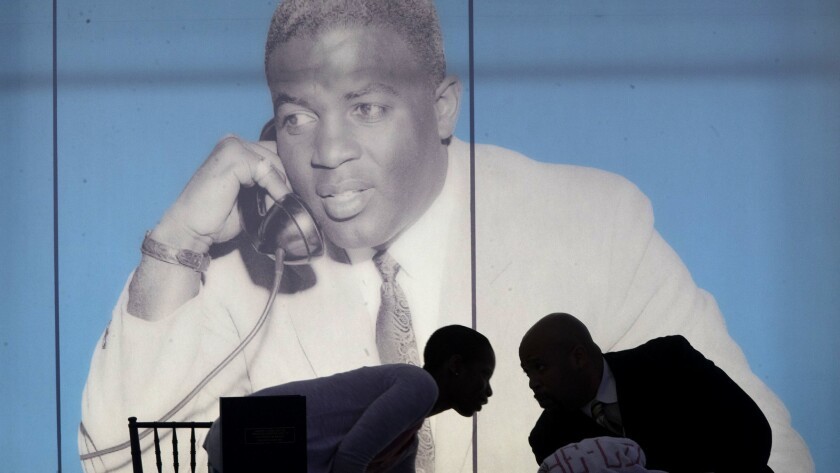 Jackie Robinson Museum employees are framed by a giant poster of legendary baseball player at a grou