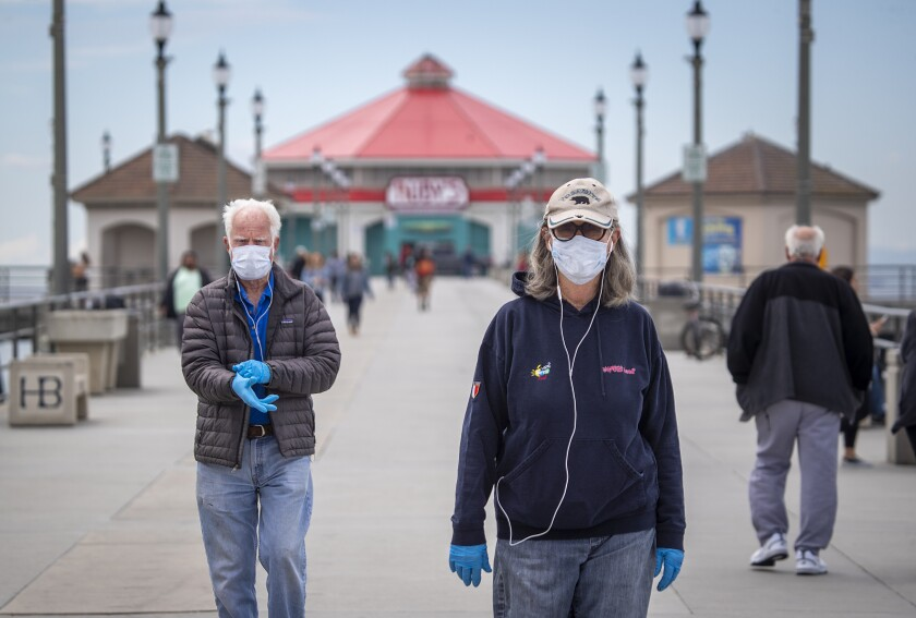 Dr. Dallas Weaver, 79, and his wife, Janet Weaver, 75, of Huntington Beach walked along the Huntington Beach pier on March 18. Officials have since closed the pier.