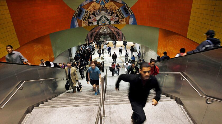 Commuters rush through the Metro Red Line station in North Hollywood. After 17 years of free parking, Metro will begin charging $3 per day to park later this month.