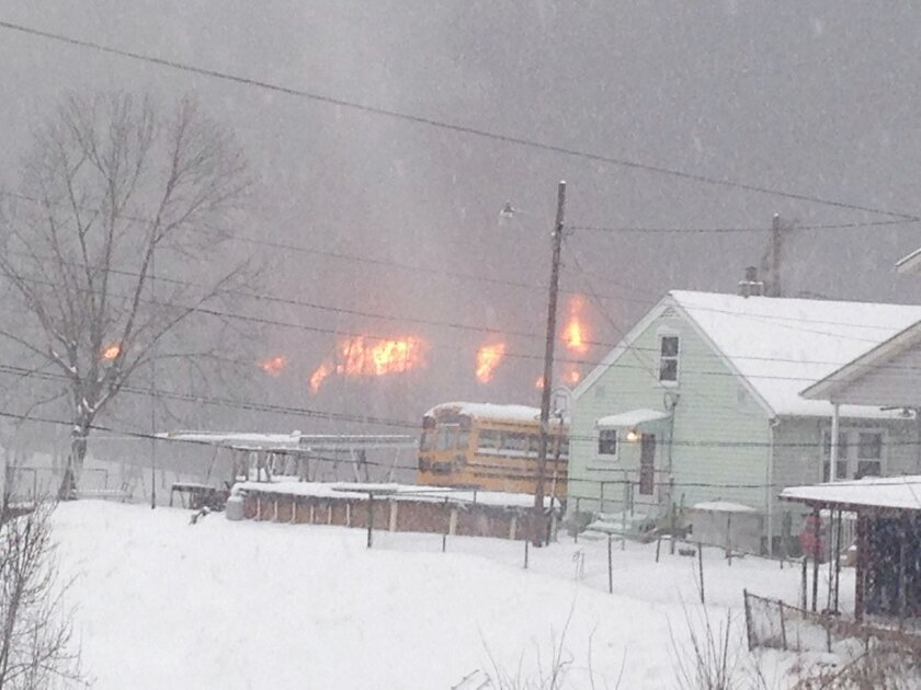 A fire burns Monday, Feb. 16, 2015, after a train derailment near Charleston, W.Va. Nearby residents were told to evacuate as state emergency response and environmental officials headed to the scene. (AP Photo/John Raby)