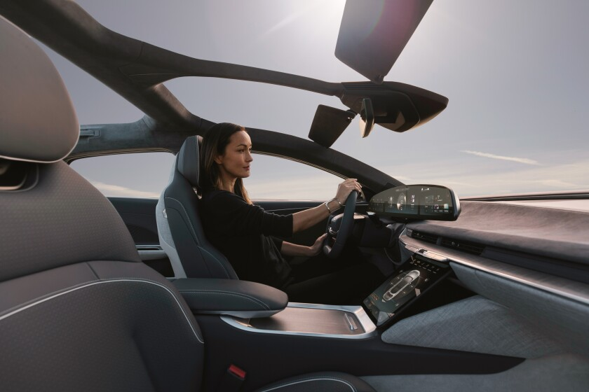 A woman at the wheel of a Lucid Air.