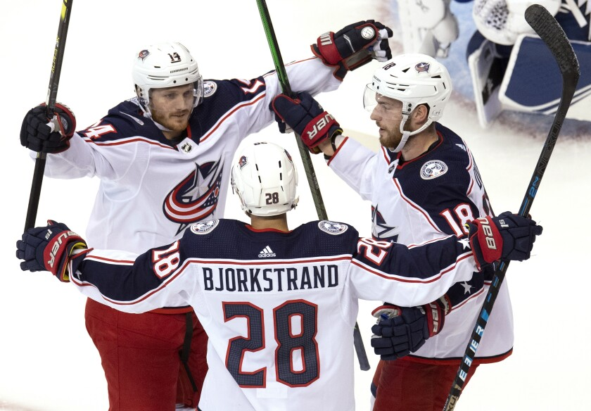 Columbus Blue Jackets right wing Oliver Bjorkstrand (28) is congratulated by teammates Gustav Nyquist (14) and Pierre-Luc Dubois (18) after scoring against the Tampa Bay Lightning during first-period of NHL Eastern Conference Stanley Cup first round playoff hockey game action in Toronto, Thursday, Aug. 13, 2020. (Frank Gunn/The Canadian Press via AP)