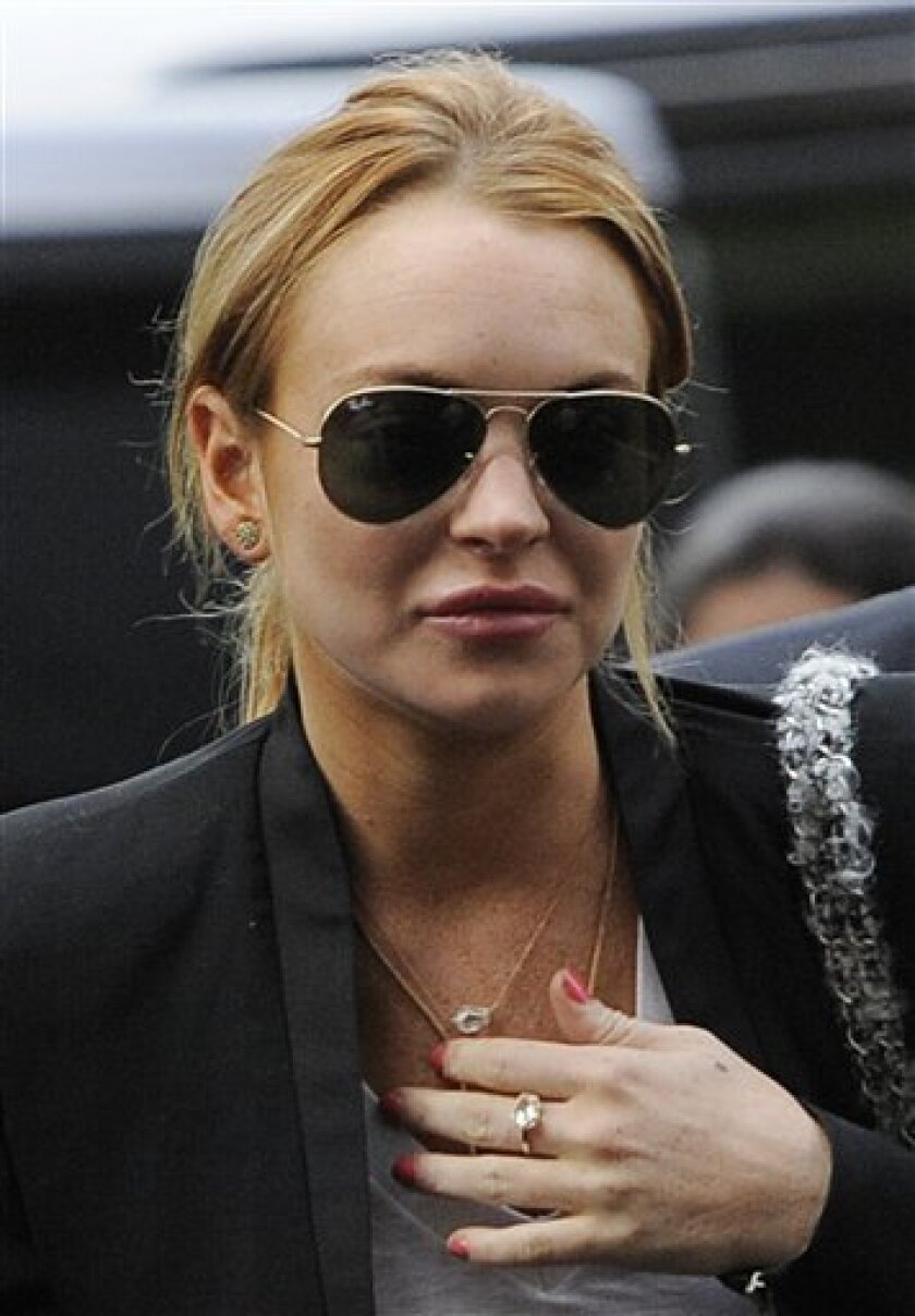 FILE - In this Oct. 22, 2010 file photo, Lindsay Lohan arrives for a probation violation hearing at Beverly Hills Courthouse in Beverly Hills, Calif. After three months in treatment, Lohan is scheduled to be released from a rehab center Monday, Jan. 2, 2011. For months, the actress has been haunted by her inability, or unwillingness, to shake a 3 1/2 year old drunken driving case that resulted in two rehab stints and two trips to jail in 2010 alone. (AP Photo/Chris Pizzello, File)