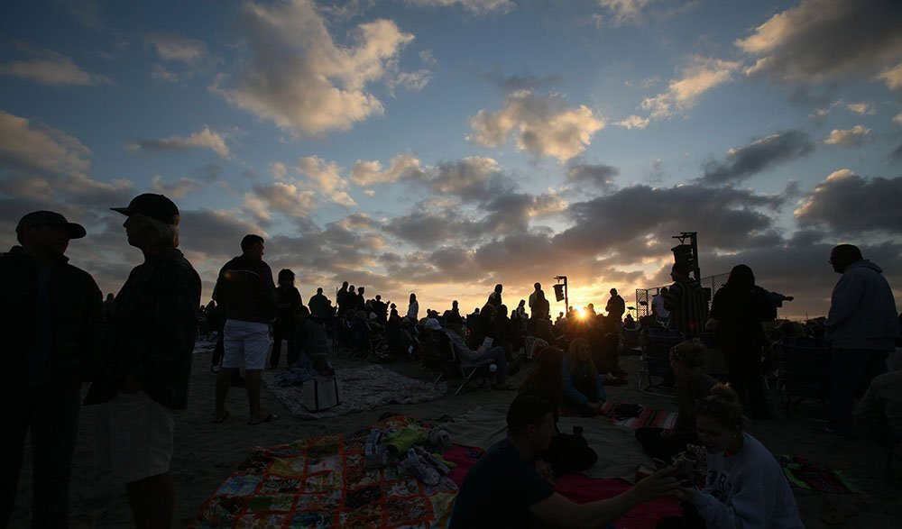 While waiting for the service to start Sunday morning, people took pictures of the sun rising and found themselves places to sit on blankets at South Ponto Beach.