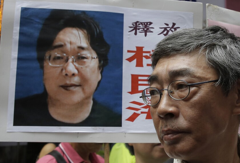A placard bearing an image of Swedish bookseller Gui Minhai serves as a backdrop for freed Hong Kong bookseller Lam Wing-kee during a June 2016 march to the Chinese government's liaison office in Hong Kong.