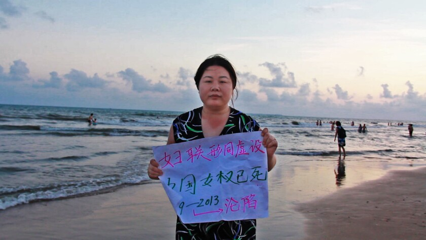 """Activist Ye Haiyan holds sign that reads, """"All China Women's Federation is a farce. China's women's rights are dead. 1949-2013 Fallen,"""" in the documentary """"Hooligan Sparrow."""""""