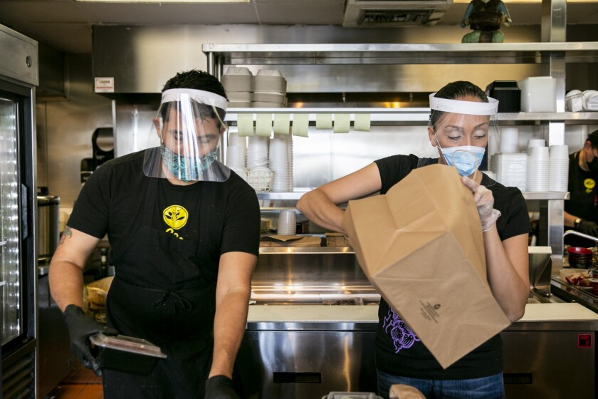 Two restaurant employees work while wearing face masks, face shields and gloves.