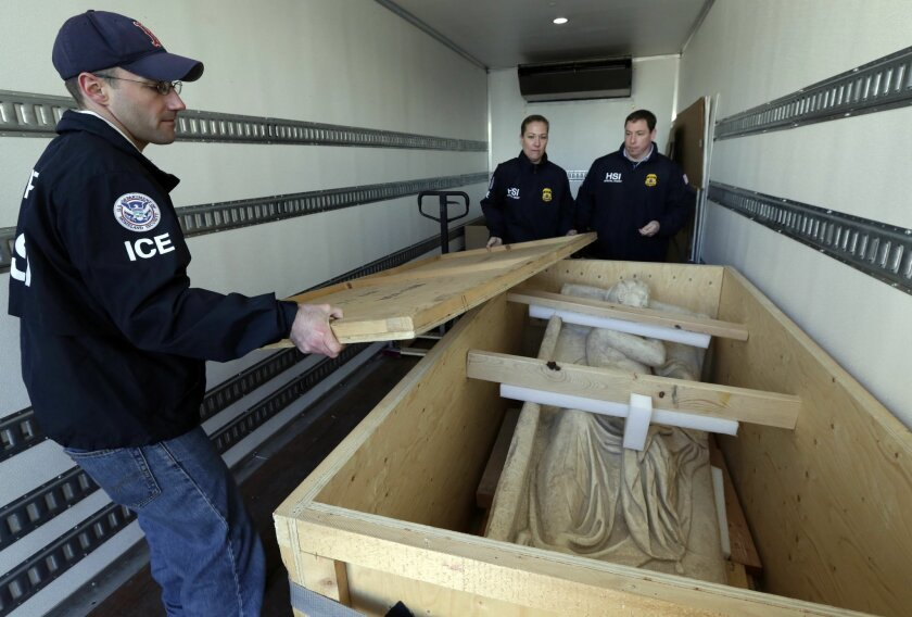 Homeland Security investigators place the top on a crate containing an ancient Roman sculpture seized at a warehouse in the Queens borough of New York, Friday, Feb. 28, 2014. Authorities said in a complaint filed in federal court Thursday that the marble statue is believed to be one of the antiquit